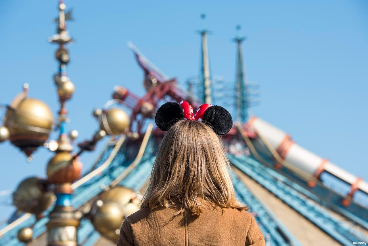 Girl with mickey ears in front of attraction